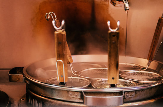 Hot boiling Ramen pot with noodle strainers and steam. Selective focus