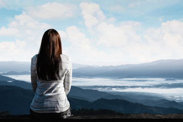 Traveler woman is sitting looking at the view of mountains natural background.