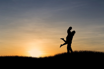 Silhouettes of couple man and woman in nature sunset background. Love concept.