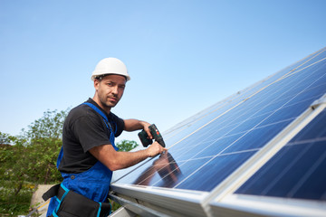 Technician installing solar panel to metal platform using electrical screwdriver on blue sky copy space background. Stand-alone solar system installation, efficiency and professionalism concept.