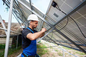 Professional engineer technician making electrical wiring standing inside high exterior solar panel photo voltaic system on bright sunny summer day. Eco friendly cheap electricity generation concept.