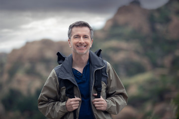 Middle-aged Caucasian male hiker trekking alone in the mountains. The overcast sky is peaceful and the man looks happy.  Depicts outdoor activity and travel tourism.