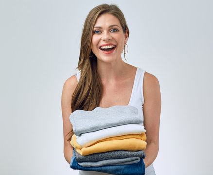 smiling woman holding stack of clothes.