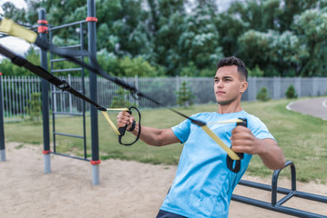 Male athlete, loops and straps training chest muscles, exercise arms shoulders. In summer spring in city. Active lifestyle, workout, fitness in fresh air. Motivation sports, green trees background.