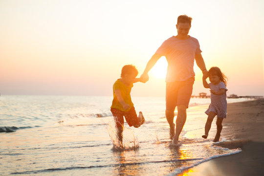 happy  family father and two children playing on the beach  run at the sunset time.