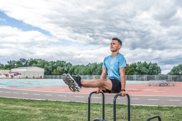 Male athlete lifting legs, exercise train muscles of abs abdomen, coach summer spring city, training on street. Active lifestyle, workout fitness fresh air. Motivation for sports. Free space for text