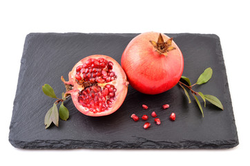 Pomegranate and seeds on black stone. Fresh tropical fruits, sweet and healthy.