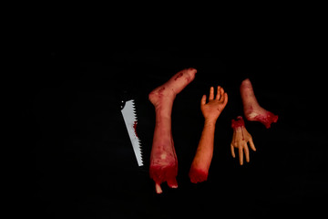 """Cut Cut Cut"" in Halloween party. Mang piece of human are sliced with blood sharp saw (fake) on black background for copy space."