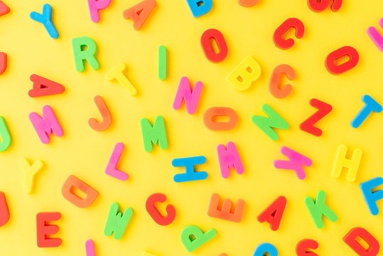 Colourful letters on yellow background - pattern. School background