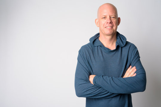 Portrait of happy mature handsome bald man smiling with arms crossed