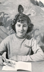 Vintage retro 1950s monochrome portrait of young girl holding a book and looking into the camera