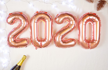 Happy New Year's Eve 2020 rose gold metallic balloons on white background, close up with copy space.