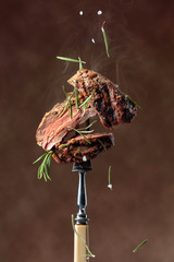 Grilled ribeye beef steak with rosemary on a brown background.