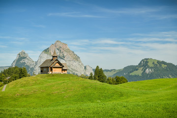 Wall Mural - Beautiful wodden church and view on Grosser Mythen peak as seen from small village of Stoos, Switzerland