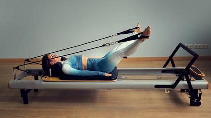 young asian woman pilates stretching sport in reformer bed instructor girl in a studio