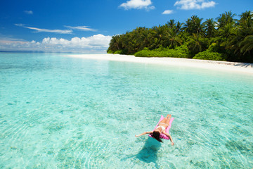 Woman swim and relax in the sea. Happy island lifestyle. White sand, crystal-blue sea of tropical beach. Vacation at Paradise. Ocean beach relax, travel to Maldives islands
