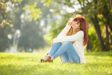 Young woman walking in the park. Beauty nature scene with colorful background at autumn season. Outdoor lifestyle. Happy smiling woman relax at fall