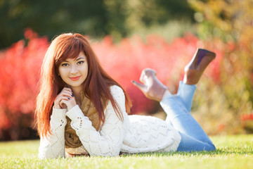 Young woman walking in the park. Beauty nature scene with colorful background, trees and leaves at fall season. Autumn outdoor lifestyle. Happy smiling woman relax on green grass