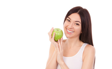 Cute woman with beautiful snow-white smile holding green apple. Healthy lifestyle and nutrition, dieting, weight loss, cosmetology, dental care and healthy teeth conсept. Close up portrait