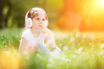 Cute little girl is listening to music in the autumn park. Family outdoor lifestyle. Happy small kid in headphones sitting on  grass. Beauty nature at fall. Childhood happiness. Children day