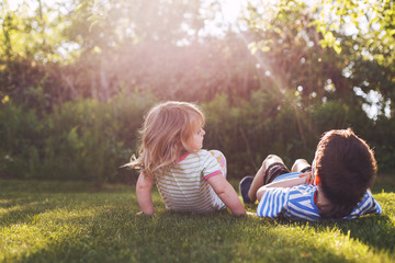 brother with  his little sister outdoor back. two children lying on the grass in the garden