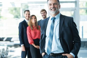 Proud smiling businessman standing with his colleagues at office