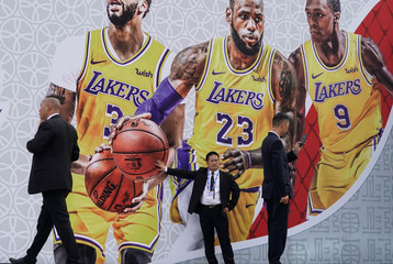 Security personnel stand in front of a billboard with an image of Los Angeles Lakers  basketball players outside the venue that was scheduled to hold fan events ahead of an NBA China game between Brooklyn Nets and Los Angeles Lakers, at the Oriental Sports