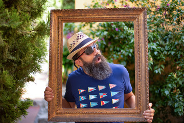 A hipster man posing inside of a picture frame