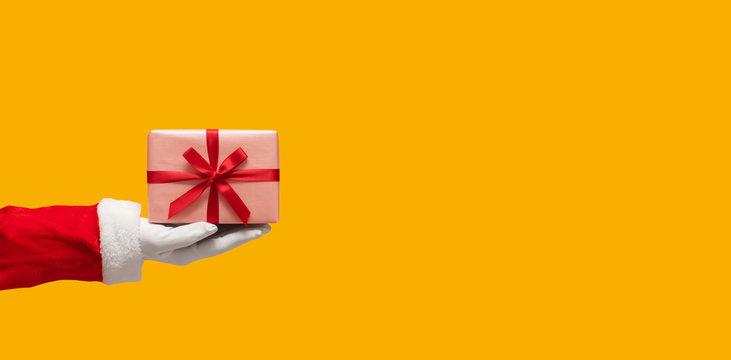 Santa Claus hand holding gift box.