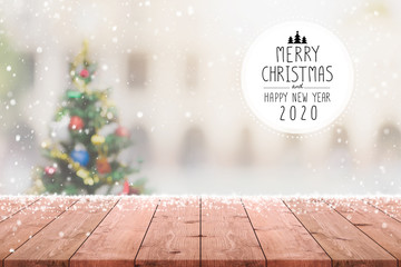 Christmas and Happy new year 2020 on empty wood table top on blur bokeh christmas tree background...