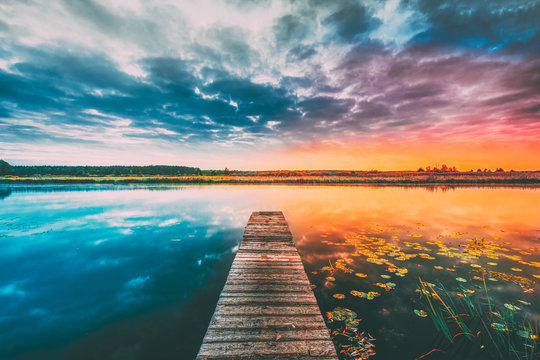 Landscape With Wooden Boards Pier On Calm Water Of Lake, River At Sunset Time, Forest On Other Side. Summer To Autumn Season Transition Concept In Nature