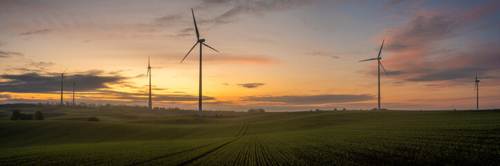 windmills on a field in Germany during a beautiful multicolored sunrise