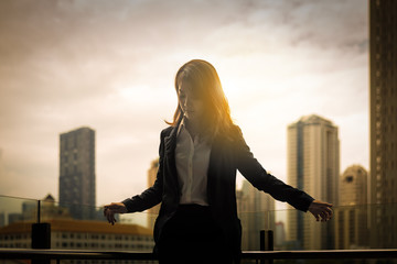silhouette of business woman in sunrise with city background