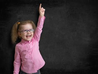 Happy kid inventor with rised hand finding idea near school black chalkboard
