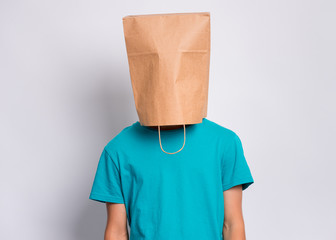 Fototapete - Portrait of teen boy with paper bag over head. Teenager cover head with bag posing in studio. Child pulling bag over head on gray background.