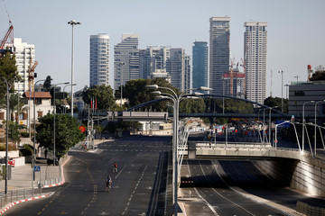 People ride their bicycles on an empty main road during the Jewish holiday of Yom Kippur in Tel Aviv, Israel