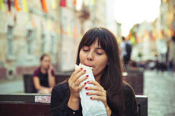 young smiling woman eating fast food outdoors