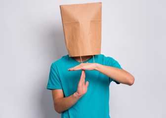 Fototapete - Portrait of teen boy with paper bag over head making timeout gesture on gray background. Child showing pause or time out sign.