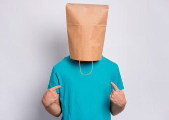 Fototapete - Portrait of teen boy with paper bag over head making fingers up gesture. Teenager cover head with bag pointing fingers on himself. Child pulling paper bag over head posing in studio.