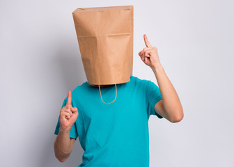 Fototapete - Portrait of teen boy with paper bag over head enjoying music and dances, on gray background. Child posing in studio.