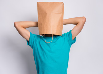 Fototapete - Portrait of teen boy, with paper bag over head taking rest, on gray background. Time to relax. Child holding hands behind his head having time-out.