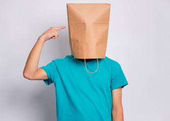 Fototapete - Portrait of teen boy show finger paper bag over head, isolated on white background. Child pointing finger at head with bag posing in studio. Teenager pulling paper shopping bag over head.