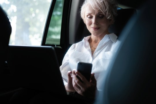 Stylish mature woman sitting on backseat of her car reading text message on mobile phone