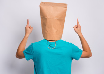 Fototapete - Portrait of teen boy - back view, with paper bag over head pointing hands up at copyspace, on gray background. Child pointing fingers at something - rear view.