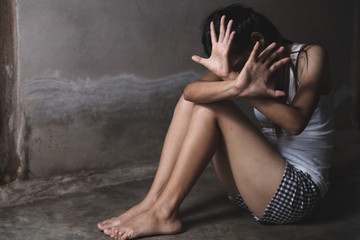 Scared young woman sitting in the corner of her bedroom, despair rape victim waiting for help,...