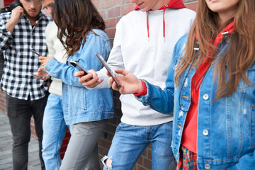Group of young people with smart phones in a row