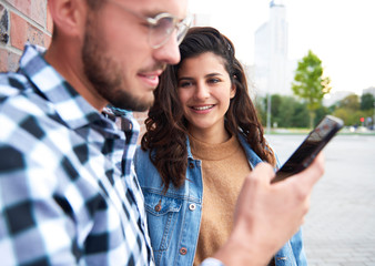 Young woman looking at man with smart phone