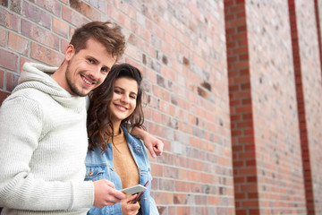 Young couple embracing and holding smart phone
