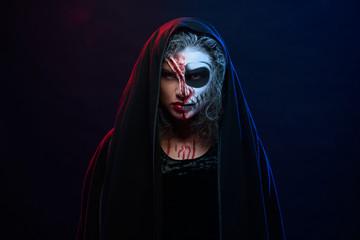 Attractive woman in halloween costume with skeleton makeup