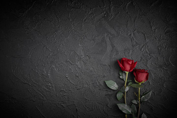 Red roses are placed on a black textured background. A sign of condolence, sympathy loss. Space for your text